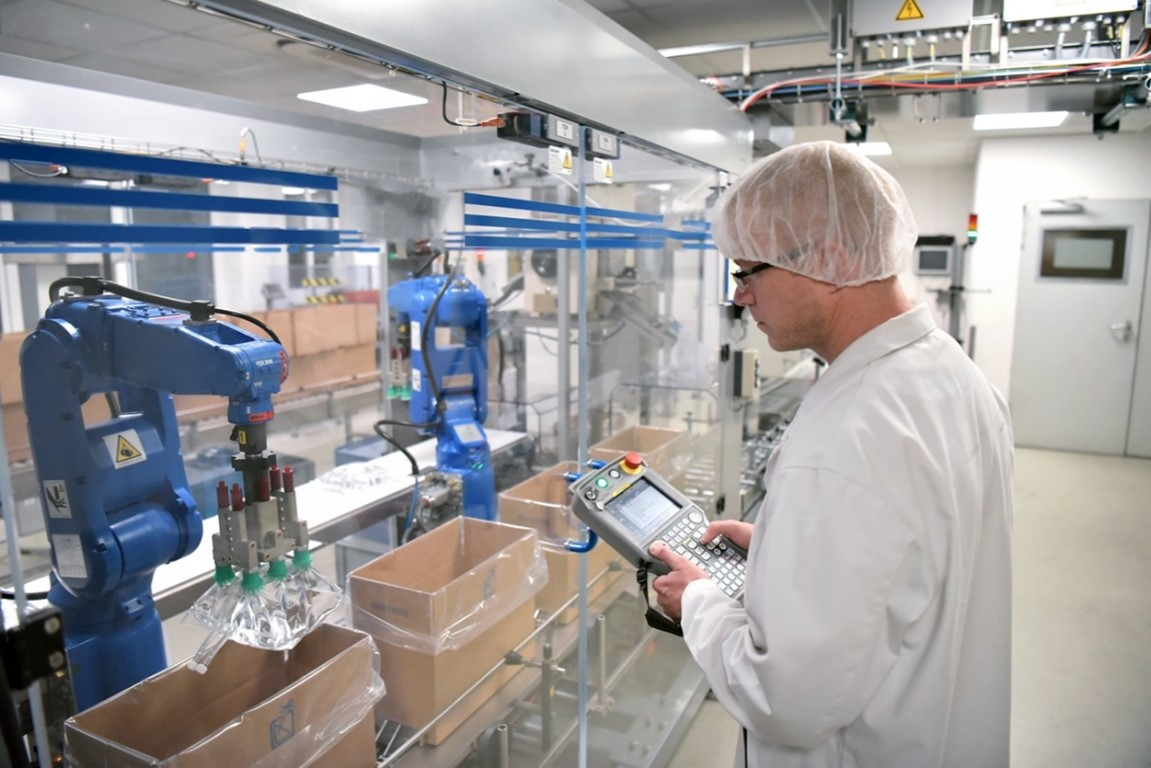 A staff dressed in a lab coat overlooking a saline bag production